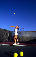 Healthy woman serving on tennis court.