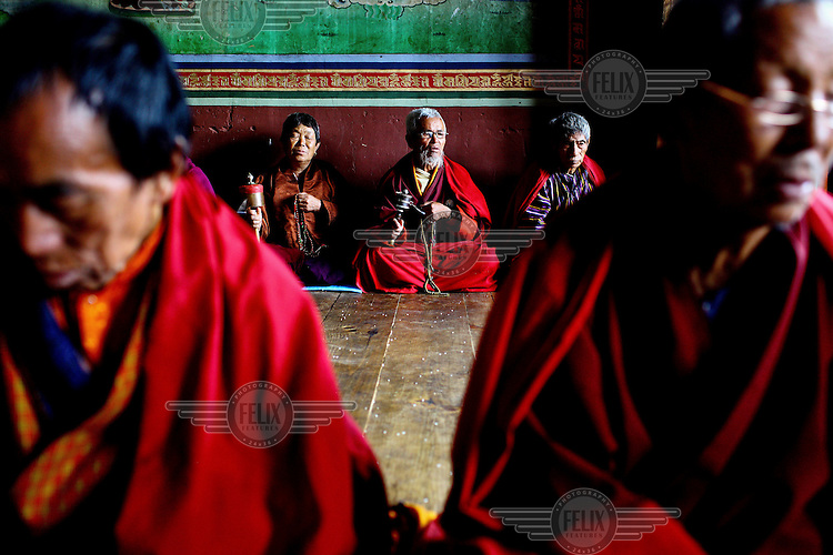 Monks in prayer at the Taktsang (Dzong) Monastery high up in the Paro Valley.
