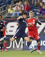 New England Revolution defender Franco Coria (2) clears the ball away from Toronto FC midfielder Gianluca Zavarise (28). In a Major League Soccer (MLS) match, the New England Revolution tied Toronto FC, 0-0, at Gillette Stadium on June 15, 2011.