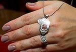 TORRINGTON, CT-122717JS05----Lori Pepler,  wife of late Torrington Fire Department Deputy Chief, Chris Pepler, shows a necklace someone had made, depicting the Torrington Fire Department badge at her home on Thursday. <br /> Jim Shannon Republican-American