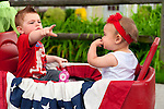 Cole Lombardo (left) of Rockville Center points out marchers to his cousin Mia Drogan (right) of Merrick, in red white and blue wagon, while watching the Merrick Memorial Day Parade on May 28, 2012, on Long Island, New York, USA. America's war heroes are honored on this National Holiday.