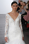 Model walks runway in a long sleeve lace sweetheart fit and flare bridal gown, from the Dennis Basso for Kleinfeld 2018 Bridal Collection on October 5 2017, during New York Bridal Fashion Week.