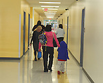 Parents and teachers direct students to their classrooms in the new wing on Monday at Katherine Smith Elementary School.