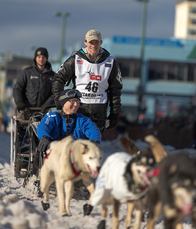 Dallas Seavey, the 2014 Iditarod champion, races his sled dog team down 4th Avenue at the ceremenial start of the 43rd Annual Iditarod in Anchorage, Alaska. Accompanying Seavey is his Iditarider Technical Sergeant Gerald Ingram.