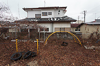 The overgrown playground of an abandoned kindergarten inside the Fukushima exclusion zone, Namie, Fukushima, Japan. Wednesday March 9th 2016. The Great East Japan Earthquake on March 11th 2011 was followed by a massive tsunami that levelled much of the Tohoku coast in north east Japan, killing around 18,000 people and causing meltdowns and explosions at the Fukushima Daiichi nuclear power station leading to the contamination and evacuation of a 20 kilometre exclusion zone around the plant.