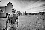 A farmer with a beard at Lowland Farms in Warwick, New York standing next to a barn and field