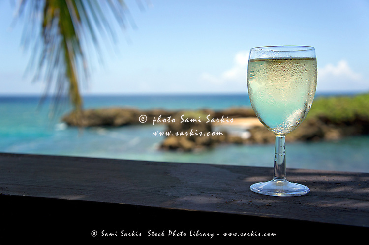 Glass of fresh white wine by tropical beach, Boca de Yuma, Dominican Republic