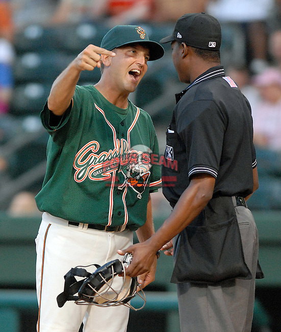 Manager Andy Haines (19) of the Greensboro Grasshoppers gives a piece of his mind to umpire Ramon DeJesus after a close call in a game against the Greenville Drive on June 14, 2010, at Fluor Field at the West End in Greenville, S.C. Photo by: Tom Priddy/Four Seam Images