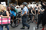 A police officer uses his bike to shove demonstrators unprovoked on State Street at Lake Street who are marching in support a Citizens Police Accountability Council to provide civilian oversight of the Chicago Police Department in Chicago, Illinois on July 11, 2016.  The demonstration attracted a larger crowd on the heels of last week's racially charged police shootings captured on video of Alton Sterling in Baton Rouge, Louisiana and Philando Castile in the St. Paul suburb of Falcon Heights, Minnesota which was followed by a mass shooting of five police officers by Afghan War veteran Micah Johnson who supported radical and violent black nationalist ideology.