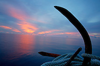 Rusty anchor with rope coiled around and view of the sunset over the sea in the background, Maldives.