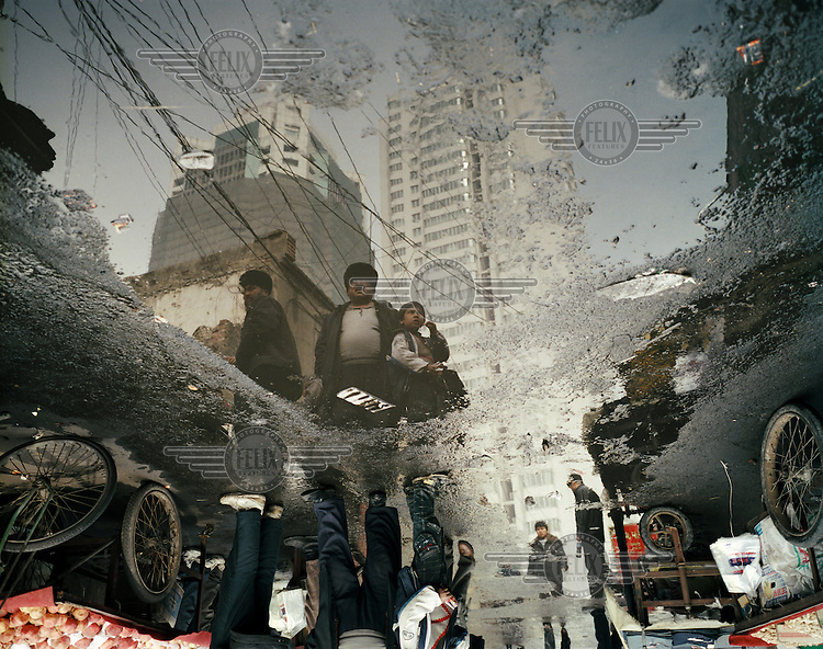 A reflection of Uighur (Uyghur) people in a melted snow puddle at the Grand Bazaar in the Uighur quarter of Urumqi.