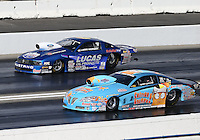 Feb. 16, 2013; Pomona, CA, USA; NHRA pro stock driver Warren Johnson (near lane) races alongside Larry Morgan during qualifying for the Winternationals at Auto Club Raceway at Pomona.. Mandatory Credit: Mark J. Rebilas-
