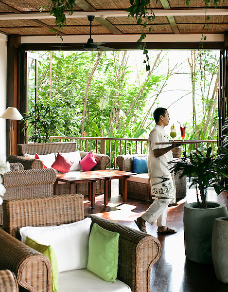 Balinese waiter carries tray of tropical fruit drinks at Bukit Becik Bar, Ubud Hanging Gardens, Bali, Indonesia.