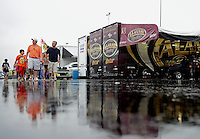 Sept. 16, 2012; Concord, NC, USA: NHRA fans walk in the rain past the hauler of top fuel dragster driver Khalid Albalooshi during a rain delay during the O'Reilly Auto Parts Nationals at zMax Dragway. Mandatory Credit: Mark J. Rebilas-