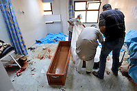 A dead rebel fighter is laid into a coffin at Tripoli Central Hospital. After a six month revolution, rebel forces finally managed to break into Tripoli and have taken control of Bab al-Aziziyah, Col Gaddafi's compound and residence. Few remain that are loyal to Gaddafi in the city; it is seeming that the 42 year regime has come to an end. Gaddafi is currently on the run. Over the recent days 50 rebel fighters have died in this hospital.