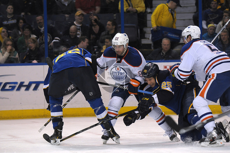 St. Louis Blues right wing Chris Stewart (25, right of center) is smashed between Edmonton Oilers center Sam Gagner (89) and Edmonton Oilers defenseman Ladislav Smid (5) as they try to get to the puck in first period action during a game between the Edmonton Oilers and the St. Louis Blues on Tuesday March 26, 2013 at the Scottrade Center in downtown St. Louis.  At far left is St. Louis Blues center David Backes (42).