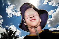 "Eight year old Peter Charles wears a hat to protect him from the sun. His mother is a nurse, so knew how to take care of him and his sister, ""I knew how to take care of the skin. Especially when they are young, albinos should be very well cared for. I always kept them inside and lotioned their skin on a daily basis."" Even with the protection of a knowledgeable and loving mother, Joyce, Peter Charles's albino sister, was recently terrified while waiting for the school bus. She overheard two men saying how they should kidnap her in order to sell her hair and skin. Discrimination against albinos is a serious problem throughout sub-Saharan Africa, but recently in Tanzania albinos have been killed and mutilated, victims of a growing criminal trade in albino body parts fuelled by superstition and greed. Limbs, skin, hair, genitals and blood are believed by witch doctors to bring good luck, and are sold to clients for large sums of money, carrying with them the promise of instant wealth."