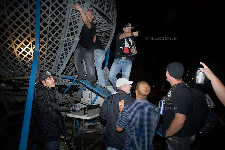 People crowd around the Globe of Death late at night at Evel Knievel Days in Butte, MT, USA.