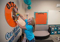 NWA Democrat-Gazette/BEN GOFF @NWABENGOFF<br /> Nanci Krapf, Osage Creek Elementary 3rd grade teacher, decorates her classroom Friday, Aug. 11, 2017, during a grand opening for Osage Creek Elementary School and Creekside Middle School in Bentonville. The new schools will welcome their first students Monday.