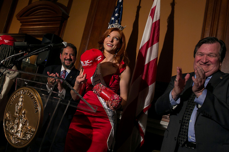 """UNITED STATES - August 27: Haely Jardas, Miss District of Columbia for 2015, looks up at her crown as she receives a """"Free DC"""" hat, in support of the District of Columbia receiving statehood, during Jardas' send off at the John A. Wilson Building in Washington, on Thursday, August 27, 2015. Jardas leaves Sunday for Atlantic City where she will compete for the Miss America 2016 title in September. (Photo By Al Drago/CQ Roll Call)"""