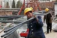 Workers transport reinforcing steel at a construction site in Beijing, China..