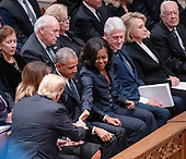 United States President Donald J. Trump reaches out to shake hands with former first lady Michelle Obama as he and first lady Melania Trump arrive for the National funeral service in honor of the late former United States President George H.W. Bush at the Washington National Cathedral in Washington, DC on Wednesday, December 5, 2018.  At top right are former US President Bill Clinton, former US Secretary of State Hillary Rodham Clinton, former US President Jimmy Carter.<br /> Credit: Ron Sachs / CNP<br /> (RESTRICTION: NO New York or New Jersey Newspapers or newspapers within a 75 mile radius of New York City)