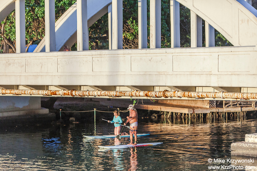 Older couple stand up paddlebarding under Anahulu Stream Bridge in Haleiwa, Oahu, Hawaii