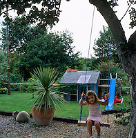 Ellie sits on a swing that hangs from a large tree in the garden