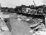 The day after the flood waters receded in Seymour, the town realized it had been split in half by the waters which destroyed bridges and a railroad trestle, that lay steaming and still in bright sunlight. This view shows the gap where once the bridge of routes 8 and 67 crossed the Naugatuck River. Further upstream the steel remains of the trestle lay half buried in the sand of the river bottom. A crane is already swinging into action.  22 August 1955.