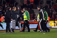 Pictured: Modou Barrow of Swansea stretchered off Sunday 01 February 2015<br />
