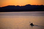 A young man paddles a sea kayak at sunrise on Jackson Lake in Grand Teton National Park, Jackson Hole, Wyoming.