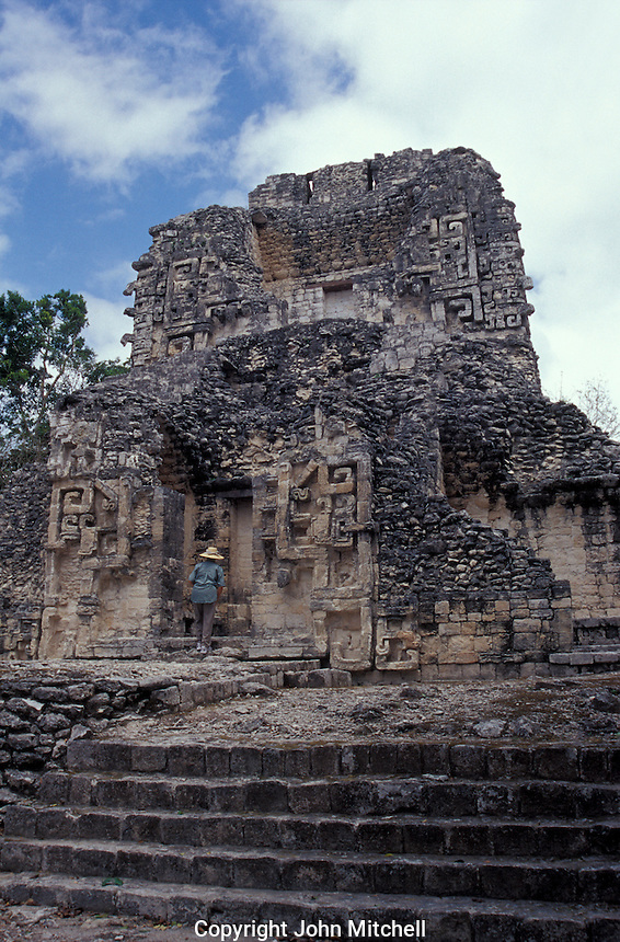 Woman entering Structure XX at the Mayan ruins of Chicanna, Campeche , Mexico. This two-storey temple is an example of Rio Bec style Mayan architecture.