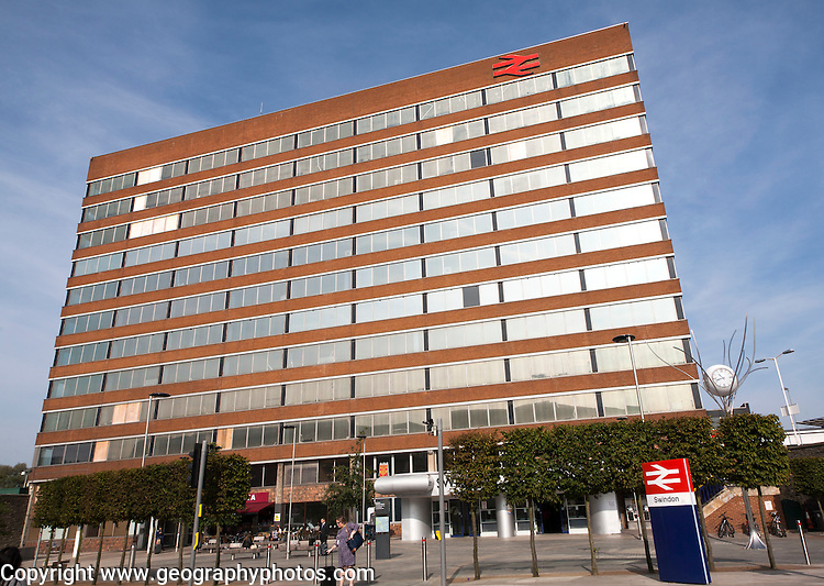 Sunshine lighting up windows of office block above the railway station at Swindon, England, UK