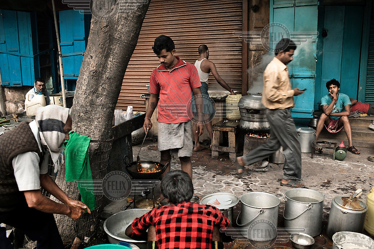 Street vendors cooking food on a pavement in Kolkata.
