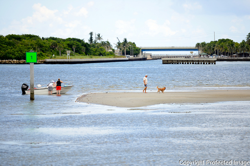 Boaters and dog enjoy walking on an exposed sandbar at low tide near the Boynton Beach, Florida, inlet.
