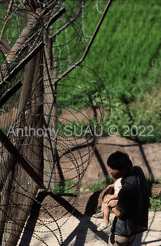 Korean DMZ<br /> P'am Mun Jeon<br /> July 3, 1988<br /> <br /> South Koreans look through the fence into North Korea at the 38th parallel DMZ which separates the two countries.