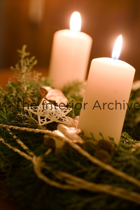 A pair of glowing candles forms the centrepiece of this Christmas decoration