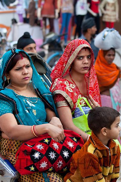 Indian women travel by rickshaw in crowded street scene in city of Varanasi, Benares, Northern India