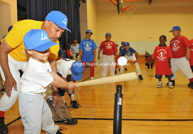 WATERBURY, CT-20 JULY 2009-072009JS03--Hector Ventura, president of Liga Deprotiva Latino Americano, a newly fromed league of mostly Dominican coaches and kids, works with his son Gabriel Ventura, 3, on a tee-ball stand prior to a gathering celebrating the new league Monday at the Baldwin Recreation Center in Waterbury. <br /> Jim Shannon Republican-American