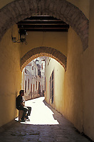 Man sitting at the entrance to a narrow alleyway or callejon in the Spanish colonial city of Zacatecas, Mexico. The historic centre of Zacatecas is a UNESCO World Heritage site.