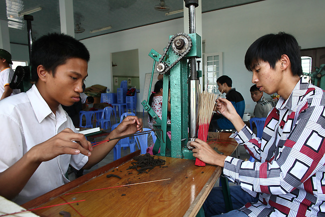 Two young men make incense sticks at a day care center for children affected by dioxin exposure near Da Nang, Vietnam. The Da Nang Association of Victims of Agent Orange/Dioxin says that more than 5,000 people -- including 1,400 children -- around the city suffer from mental and physical disabilities caused by dioxin exposure, the result of the U.S. military's use of Agent Orange during the Vietnam War more than 40 years ago. About 200 children attend three centers operated by the group, where they are taught to read and write and socialize with other children. Some young adults are taught how to sew, make incense and handicrafts, with the goal of enabling them to work and make money for themselves and their families. The Vietnam Red Cross says that more than 3 million people suffer from illnesses related to Agent Orange and dioxin exposure, including at least 150,000 children born with severe birth defects since the end of the war. The U.S. government started paying last year to clean up dioxin-contaminated soil at the Da Nang airport, which served as a major U.S. base during the conflict. However, the U.S. government still denies that dioxin is to blame for widespread health problems in Vietnam and has never provided any money specifically to help the country's Agent Orange victims. March 18, 2013.