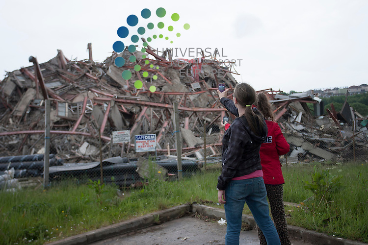 Crowds gathered to watch the demolition of the a tower block at Petershill Drive in Glasgow this afternoon as part of a plan to demolish all tower blocks in Glasgow in the next few years. Pictured: Children photograph the remaining rubble...Picture: Jonathan Faulds / Universal News And Sport (Europe)