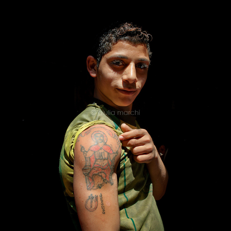 Egypt / Cairo / 22.3.2012 / A young man show his 'Jesus' tattoo in the Coptic area of Moqattam district in Cairo. Here lives a minority Coptic religious community, the Zabbaleen, who have served as Cairo's informal rubbish collectors for the past decades. Egypt, March 2012.