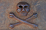 Rusty human skull with crossed bones cast from iron Danger and death symbol