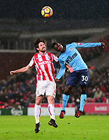 Joe Allen of Stoke battles for a header with Christian Atsu of Newcastle during the EPL - Premier League match between Stoke City and Newcastle United at the Britannia Stadium, Stoke-on-Trent, England on 1 January 2018. Photo by Bradley Collyer / PRiME Media Images.