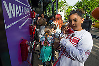 NWA Democrat-Gazette/BEN GOFF @NWABENGOFF<br /> Madison Osbon, 10, of Bentonville listens to a recording Friday, May 10, 2019, at the Inclusion Town area at Compton Gardens during the Bentonville Film Festival. The phones are part of the Check Your Blind Spots Tour presented by CEO Action for Diversity & Inclusion. The tour presented a variety of interactive experiences designed to help guests learn about unconcious bias they may hold.