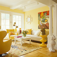 One end of the sunny yellow dining room is furnished with a sofa and armchairs, the large painting above the sofa is by Renee Demsey