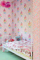 A child's bedroom is furnished with a painted wrought iron bed and has walls covered with pretty floral wallpaper