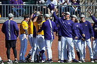 Alec Burleson (19) of the East Carolina Pirates is congratulated by teammates as he returns to the dugout after hitting a solo home run in the top of the first inning against the Charlotte 49ers at Hayes Stadium on March 8, 2020 in Charlotte, North Carolina. The Pirates defeated the 49ers 4-1. (Brian Westerholt/Four Seam Images)