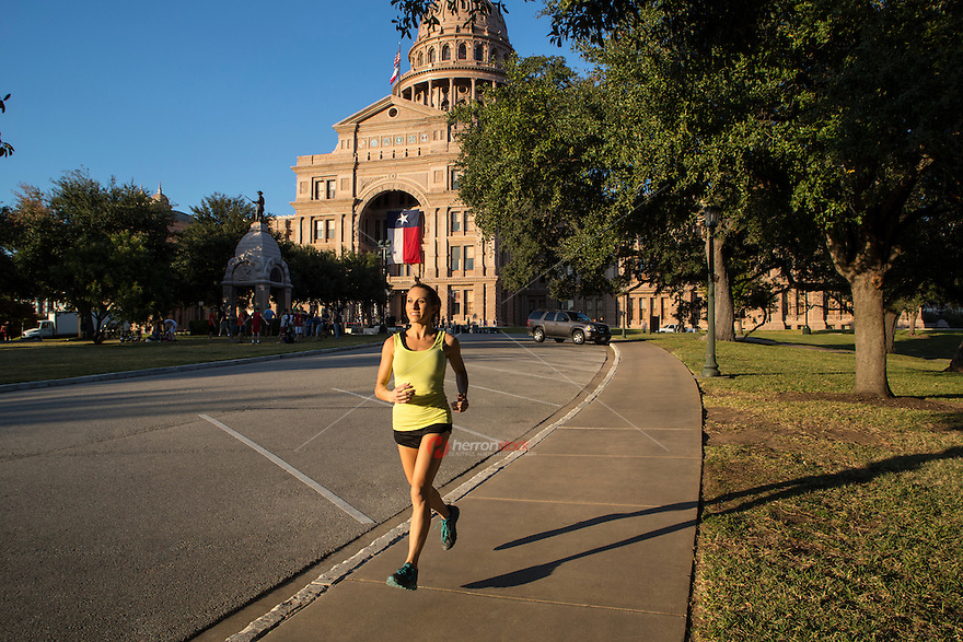 Beautiful fit female runner jogging along the Texas State Capitol on a sunny Austin summer day in downtown Austin, Texas.